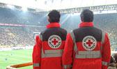 Foto: Zwei Sanitäter stehen im Fußballstadion und blicken auf das Feld. Dieses Foto ist gleichzeitig ein Link und führt Sie zu der Unterseite: Sanitätsdienst.